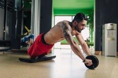 Sterke mens in de gymnastiek die abs oefening doen stock afbeeldingen