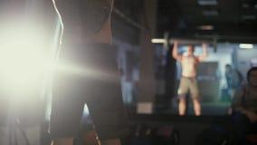 Sterke mens die barbell snatch oefening doen bij de gymnastiek in langzame motie Sportvrouw op oefeningsmat die situps in gymnast stock video