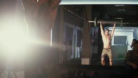Sterke mens die barbell snatch oefening doen bij de gymnastiek in langzame motie Sportvrouw op oefeningsmat die situps in gymnast stock videobeelden