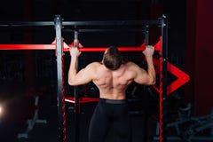 Sterke mens die trekkrachtups knappe atleet doen bij gymnastiek grote zekere spier opleiding Stock Afbeeldingen