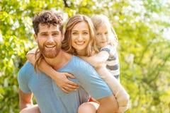 Sterke mens ondersteunend zijn familie door vrouw en zoonsvervoer per kangoeroewagen te dragen royalty-vrije stock foto