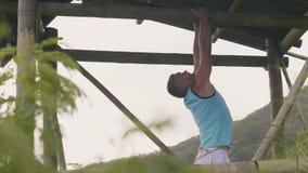 Sterke mens opleidingstrekkracht UPS op houten dwarsbalk terwijl training openlucht Geschiktheid die trekkrachtups oefening op re stock videobeelden