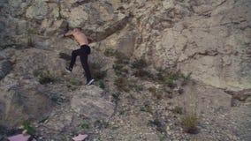 Sterke mensenjogging op de ruwe rots en opleidings vrije strijd 4K stock videobeelden