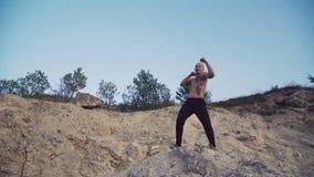 Sterke mensenjogging op de ruwe rots en opleidings vrije strijd 4K stock video