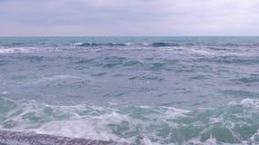 Sterke onweersgolven die tegen de golfbreker op de waterkant slaan stock videobeelden