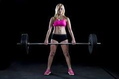 Sterke sexy vrouw deadlifts heel wat gewicht Stock Afbeelding