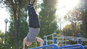 Sterke spiermens die een handstand in een park doen Geschikte spier mannelijke geschiktheidskerel die stunts op rekstokken doen o Royalty-vrije Stock Afbeeldingen