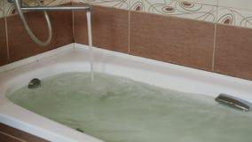 Sterke straal die van water van de tapkraan in de ton stromen Volledig bad stock videobeelden