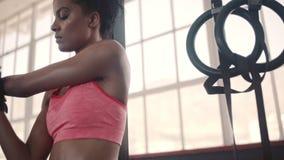 Sterke vrouw die haar wapens uitrekken bij gymnastiek stock video
