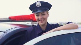 Sterke vrouw in politie eenvormige status dichtbij patrouillewagen het glimlachen, wet en orde stock videobeelden