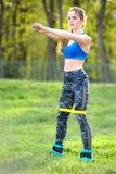 Sterke vrouw in sportkleding die hurkzit doen Foto van het spiergeschiktheid model werken stock afbeeldingen