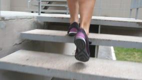 Sterke vrouwelijke benen in sportschoenen die op treden tot gymnastiek naar opleiding gaan Vrouw die naar gezondheidsclub voor tr stock video