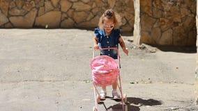 Sterke wind orkaan Moeder op een gang met haar baby in een wandelwagen Het kindmeisje speelt een spel van moederschap  stock footage