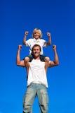 Sterke zoonszitting op de schouders van zijn vader Stock Afbeeldingen