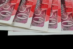 Sterling notes. Five fifty pound notes  on a black background