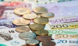 Sterling- und Eurobanknoten und Münzen Stockbilder