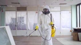 Sterminatore in camici e una maschera protettiva con uno spruzzatore video d archivio