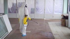Sterminatore in vestiti speciali ed in un antiparassitario degli spruzzi della maschera protettiva, retrovisione video d archivio