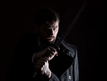 Stern angry businessman in a wool coat with sword in dark background Stock Photography