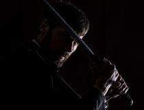 Stern angry businessman in a wool coat with sword in dark background Royalty Free Stock Photos