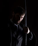 Stern angry businessman in a wool coat with sword in dark background Royalty Free Stock Image