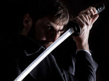 Stern angry businessman in a wool coat with sword in dark background Royalty Free Stock Photo