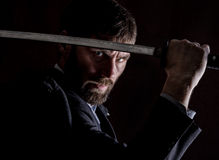 Stern angry businessman in a wool coat with sword in dark background Stock Photos