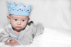 Stern Baby Wearing Blue Knit Crown. Baby with blue eyes lying on his back looking to the side with a thoughtful and stern expression wearing a light blue knit Royalty Free Stock Photos