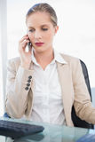 Stern blonde businesswoman having a phone call posing Royalty Free Stock Images