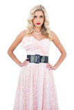 Stern blonde model in pink dress posing hands on the hips and looking at camera Royalty Free Stock Photos