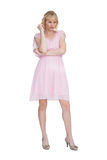 Stern blonde in pink dress posing Stock Image