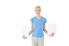 Stern blonde woman holding sheets of paper Royalty Free Stock Image