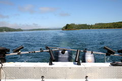 Stern of boat in sea. Stern or back of fishing boat in sea with forested coastline in background royalty free stock image