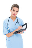 Stern brown haired nurse in blue scrubs filling an agenda Royalty Free Stock Photos