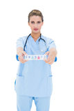 Stern brown haired nurse in blue scrubs showing a medication box Royalty Free Stock Photos