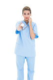 Stern brown haired nurse in blue scrubs using a stethoscope Stock Images