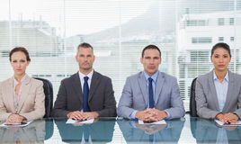 Stern business people sitting straight looking at camera Stock Images