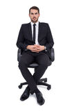 Stern businessman sitting on an office chair Royalty Free Stock Image