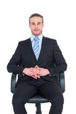 Stern businessman sitting on an office chair Stock Photos