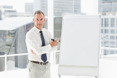 Stern businessman standing at whiteboard with marker Royalty Free Stock Photography