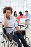 Stern businessman in wheelchair holds planner and frowns at camera Royalty Free Stock Photo