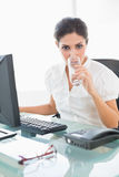 Stern businesswoman drinking a glass of water at her desk Royalty Free Stock Images