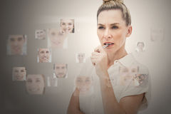 Stern businesswoman encircled by digital interface. Showing faces Stock Photo