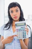 Stern businesswoman holding a calculator Stock Photo
