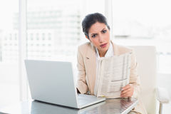 Stern businesswoman holding newspaper while working on laptop lo Royalty Free Stock Image