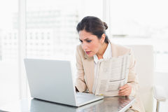 Stern businesswoman holding newspaper while working on laptop Royalty Free Stock Photos