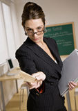 Stern businesswoman holding ruler and notebook. Stern, disciplinarian businesswoman holding ruler and notebook Stock Images
