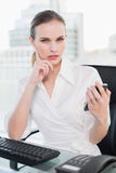 Stern businesswoman sitting at desk sending a text Royalty Free Stock Image