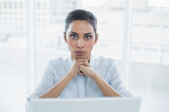 Stern businesswoman sitting at her desk looking at camera Royalty Free Stock Image