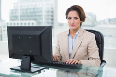 Stern businesswoman sitting looking at camera Royalty Free Stock Images